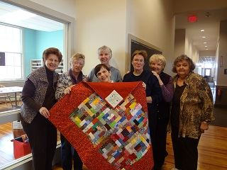 Seniors Displaying a Quilt